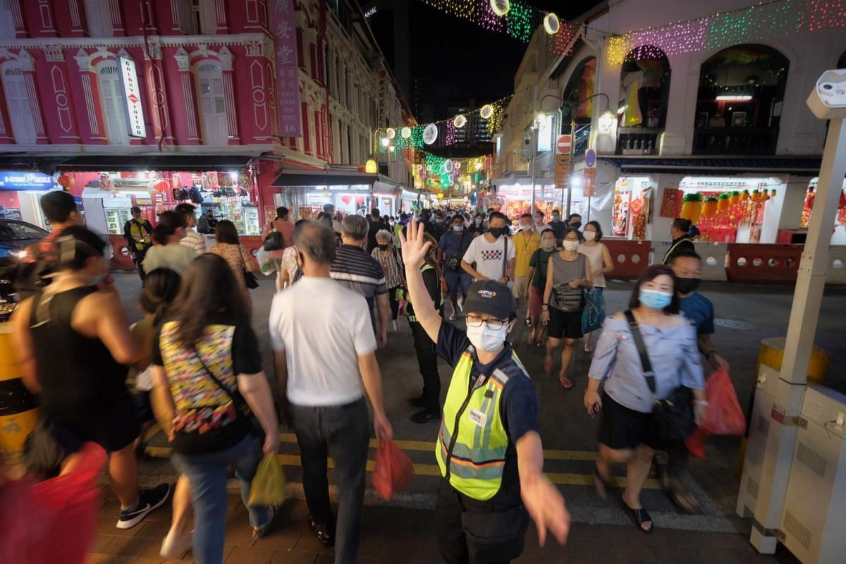 Certis Cisco crowd control officers directing pedestrian traffic at a junction along Trengganu Street in Chinatown on Feb 6, 2021.
