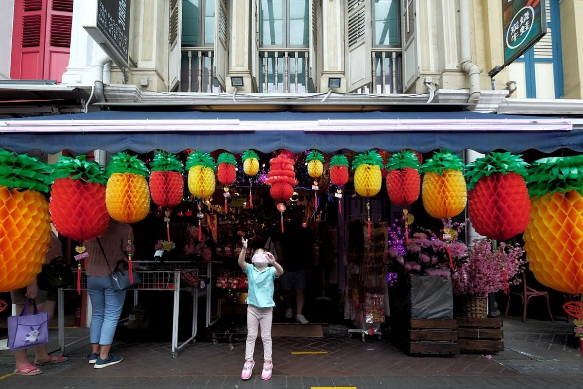 A child trying to reach the Chinese New Year decorations hung outside a shop in Chinatown on Jan 24, 2021.
