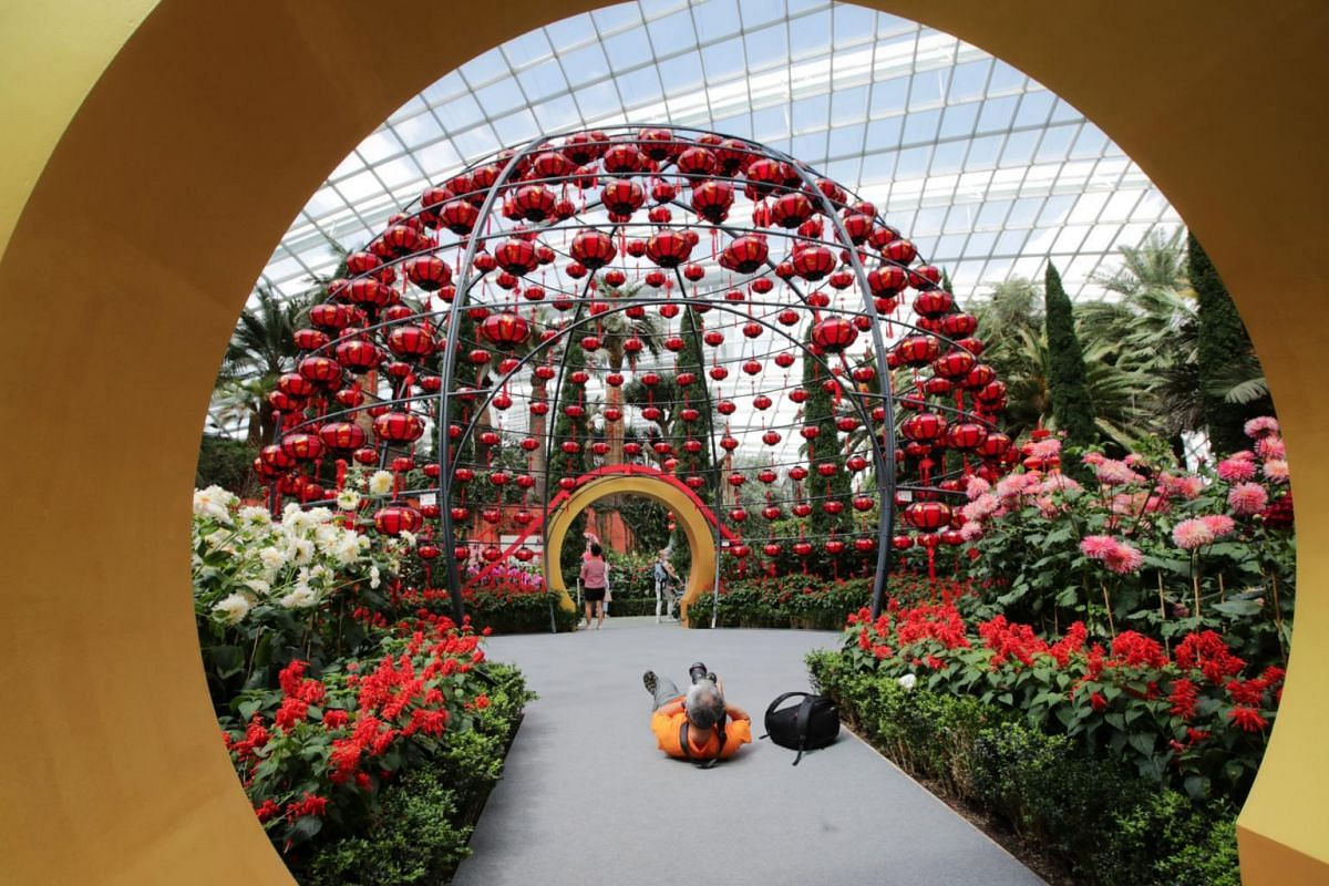 A photographer taking picture of the Lantern Globe while laying down on the floor at the Flower Dome, Garden by the Bay on Jan 15, 2021.