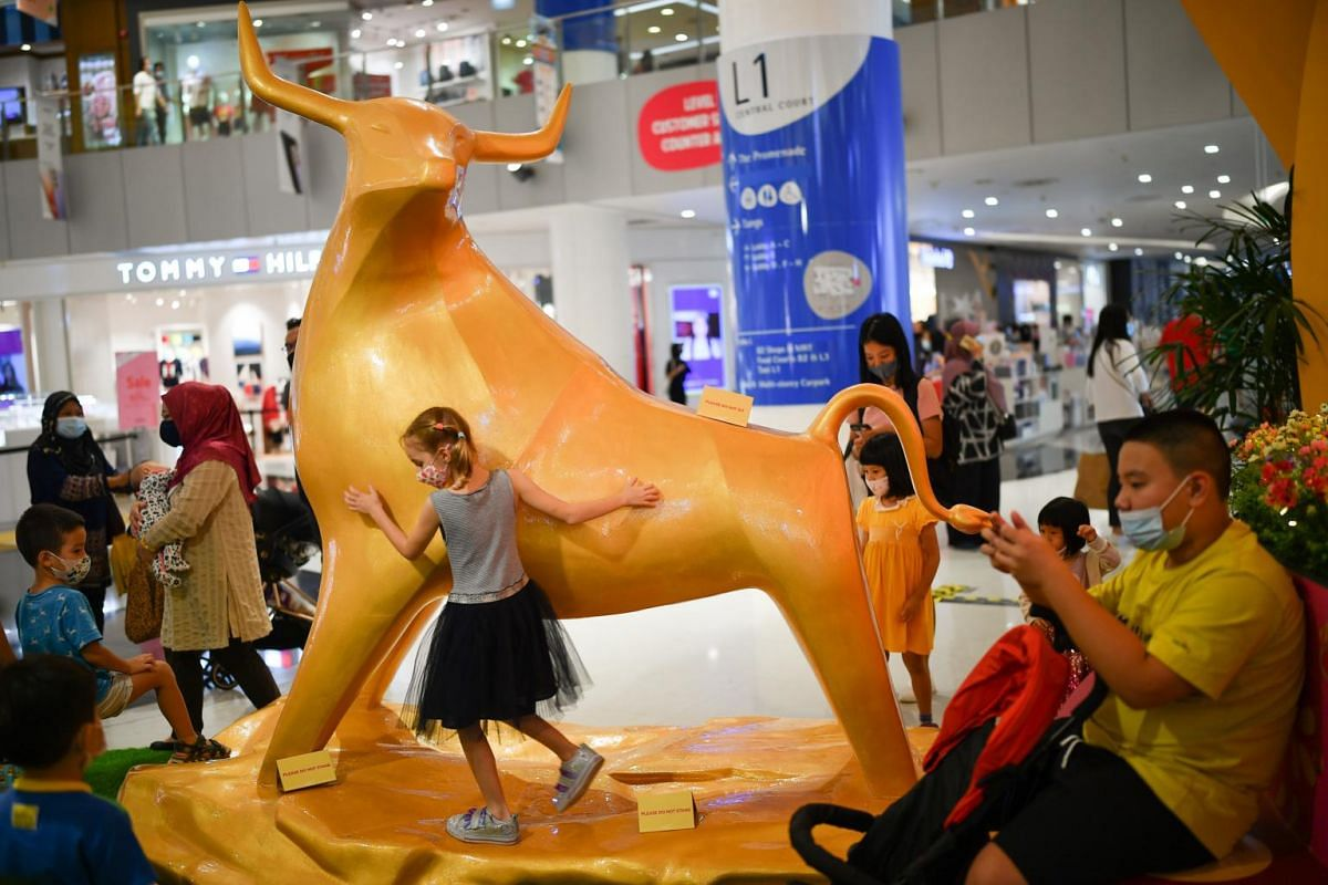 Children playing at an ox statue that is among the Chinese New Year displays at VivoCity on Jan 15, 2021.