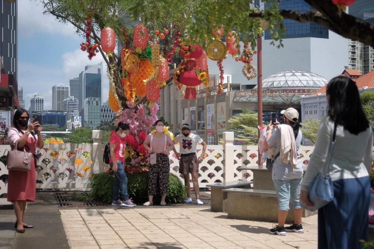 A group of friends taking pictures at a tree with Chinese New Year decorations on an overhead bridge in Chinatown on Jan 24, 2021.