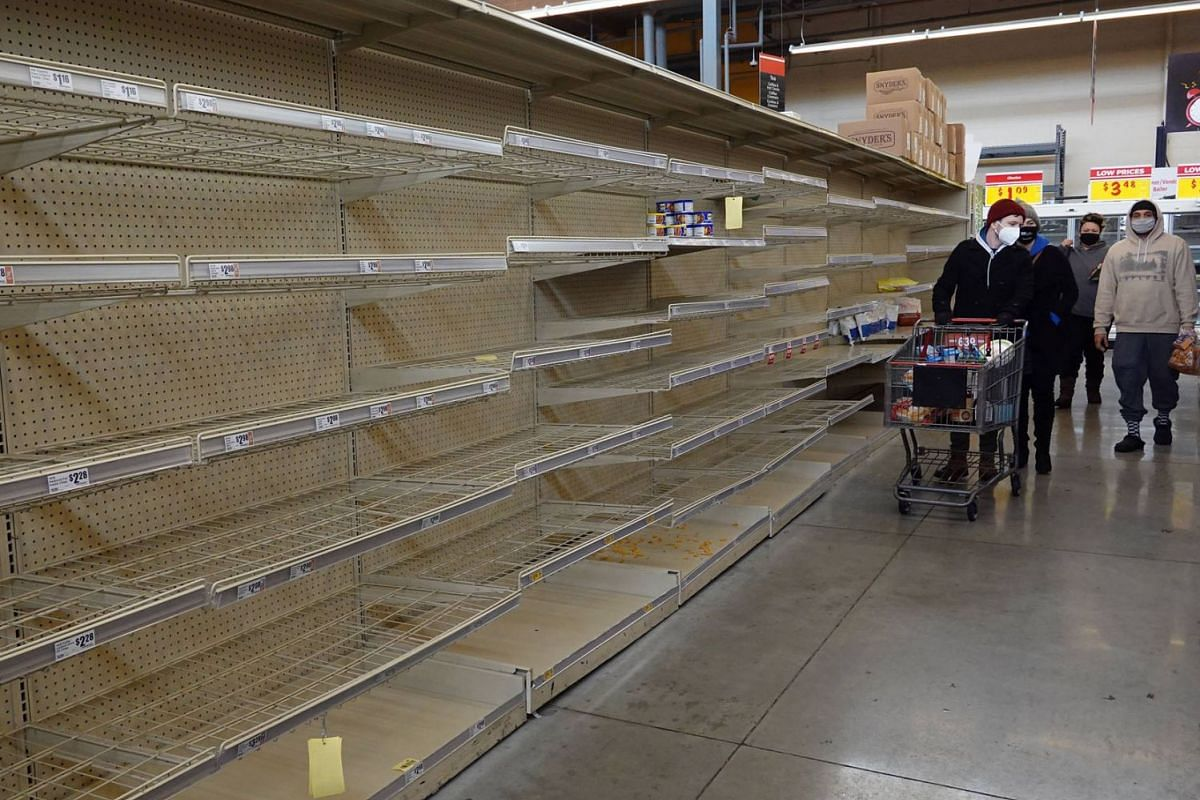Shoppers walk past a bare shelf as people stock up on necessities at the H-E-B grocery store on Feb 18, 2021 in Austin, Texas.