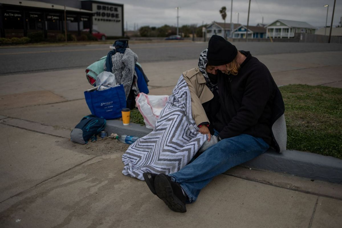 Couple Renne Alva, 37, and Travis Wasicek, 43, sit amongst their belongings along Seawall Boulevard as they embrace to keep each other warm after record-breaking winter temperatures in Galveston, Texas, U.S., Feb 18, 2021. The couple said they became