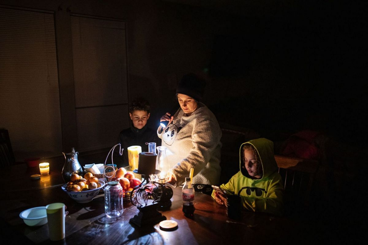 Manessa Grady adjusts an oil lamp while spending time with her sons Zechariah, 8, left, and Noah, 9, at their home in Austin, Texas, on Feb. 16, 2021, which has been without power since early Monday morning.