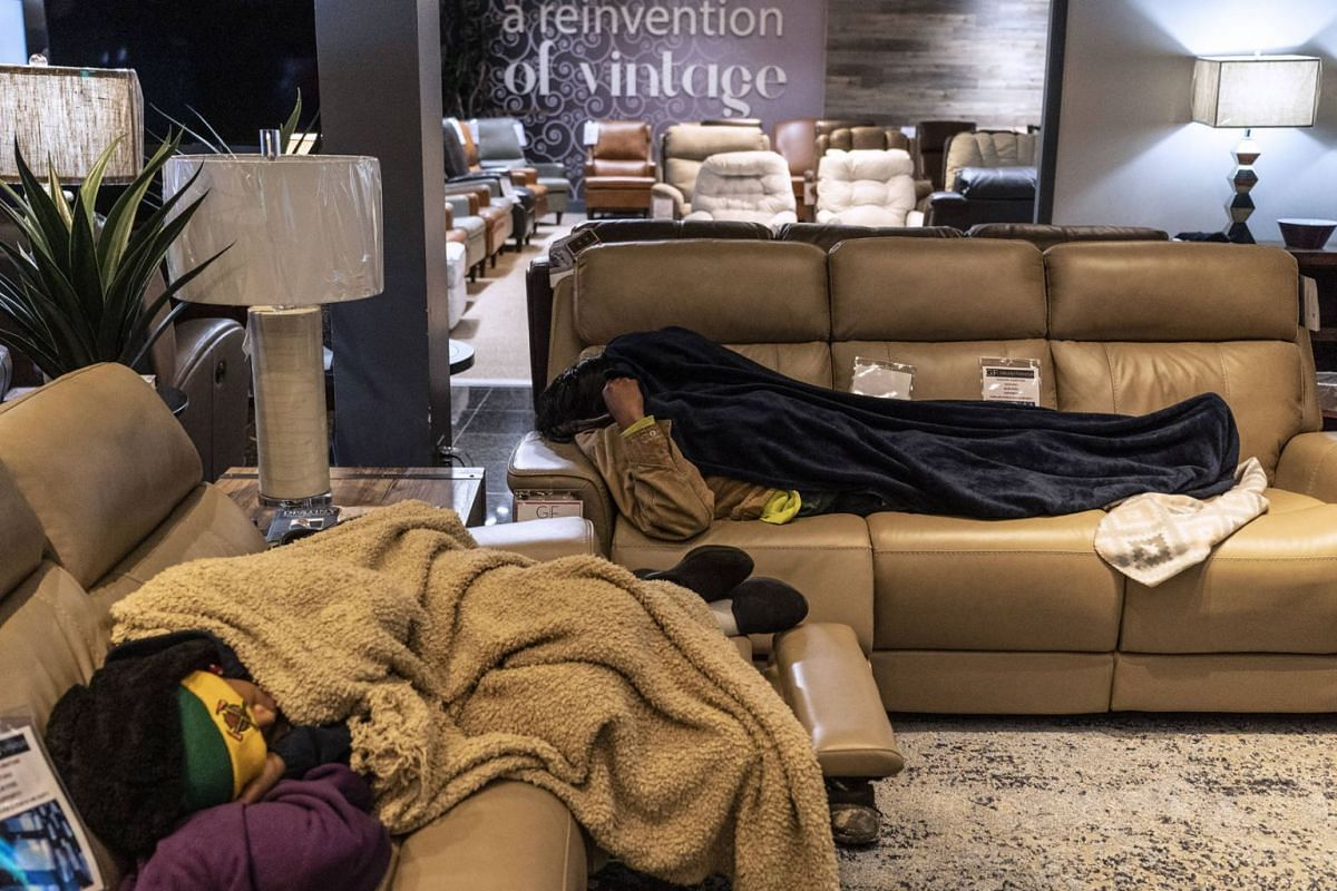 People sleep on couches while taking shelter at Gallery Furniture store which opened its door and transformed into a warming station after winter weather caused electricity blackouts on Feb 18, 2021 in Houston, Texas. Winter storm Uri brought severe