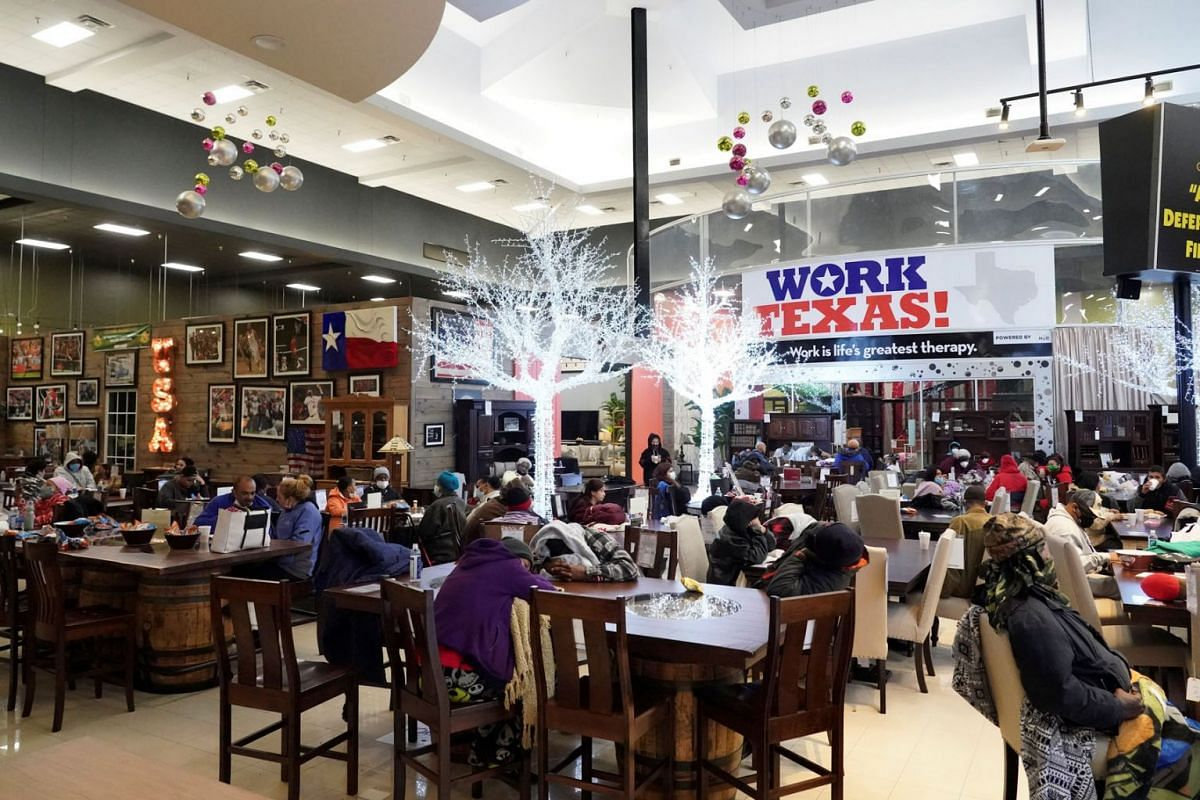 People take shelter at Gallery Furniture store which opened its door and transformed into a warming station after winter weather caused electricity blackouts in Houston, Texas, U.S. Feb 17, 2021.