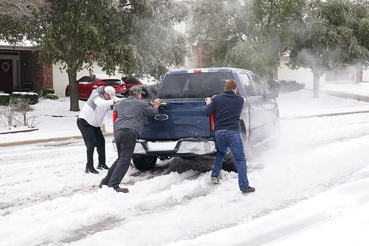 Residents help a pickup driver get out of ice on the road in Round Rock, Texas, on Feb 17, 2021, after a winter storm.