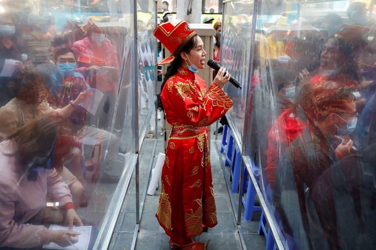 A gold shop employee is dressed as the God of Wealth at a jewellery shop on God of Wealth Day, which falls on the 10th day of Lunar New Year, as Vietnamese hope buying gold would bring good luck, in Hanoi, Vietnam, Feb 21, 2021.