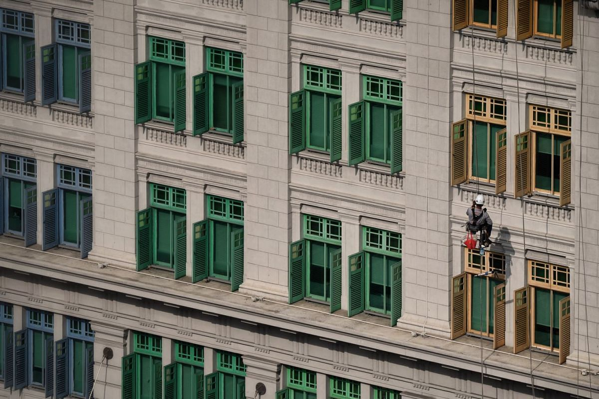 A worker is seen cleaning the facade of the Ministry of Communications and Information (MCI) building on Feb 18, 2021.