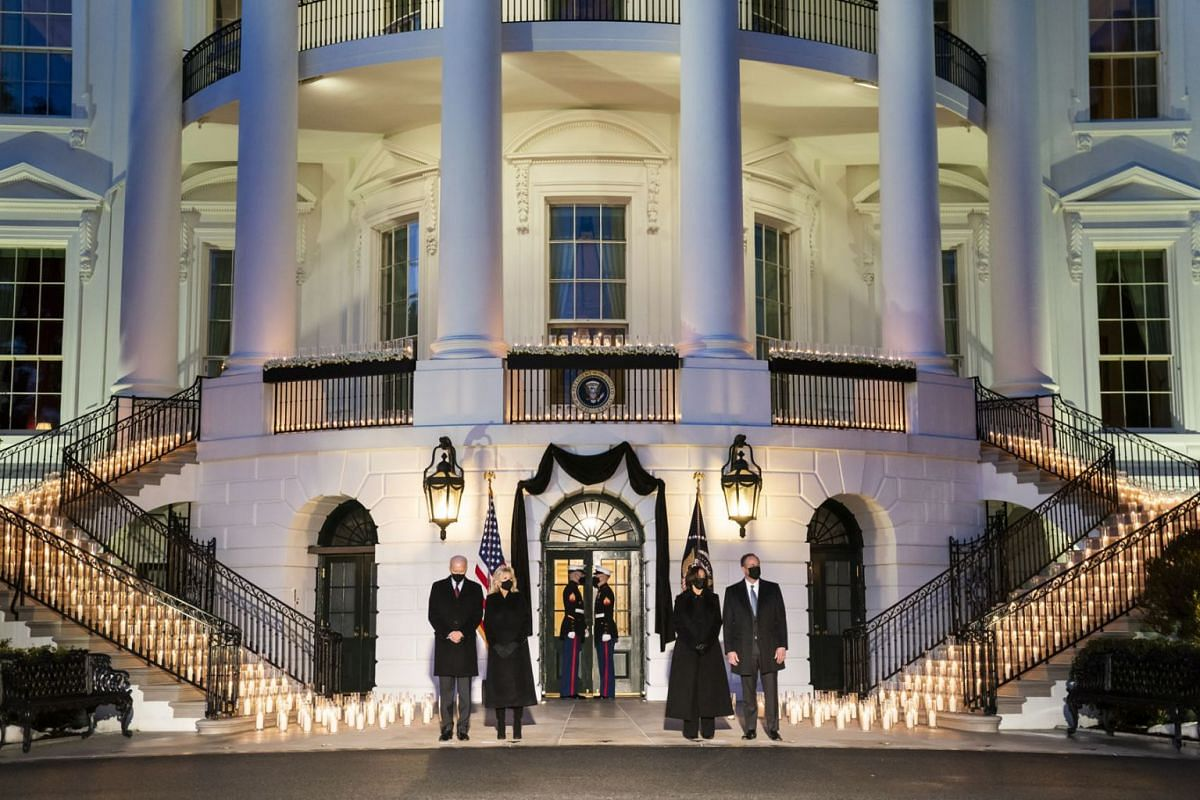 US President Joseph Biden (L), First Lady Jill Biden (C-L), Vice President Kamala Harris (C-R) and Second Gentleman Doug Emhoff (R) hold a moment of silence and candle lighting ceremony on the South Portico of the White House for the 500,000 American
