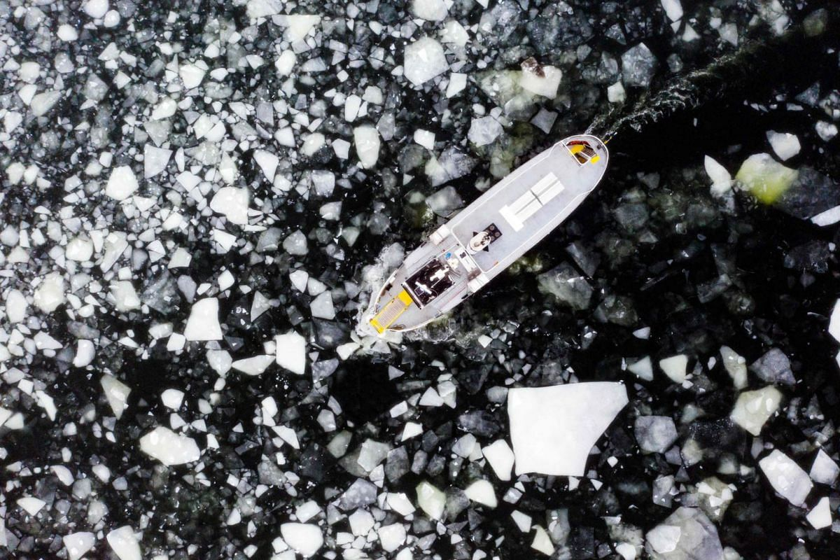 Aerial view shows a boat making its way through the icy water of Lidingo, near Stockholm, Sweden, on Feb 22, 2021.