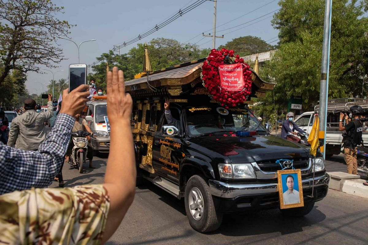 Protesters hold up the three finger salute during a funeral for Thet Naing Win, who died from a gunshot wound while taking part in a demonstration against the military coup last week, in Mandalay on Feb 23, 2021.