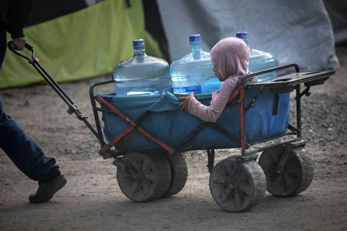 Asylum seekers carry fresh water distributed at a migrant camp at the U.S.-Mexico border on Feb 23, 2021 in Matamoros, Mexico.