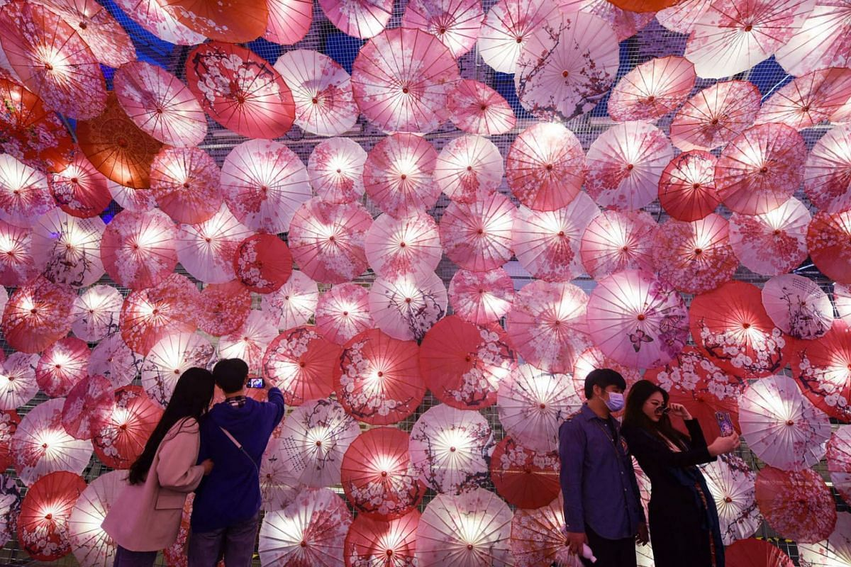People taking selfies next to a display of umbrellas decorated with lights for the upcoming Lantern Festival on a commercial street in Hangzhou, in eastern China's Zhejiang province on Feb 22, 2021.