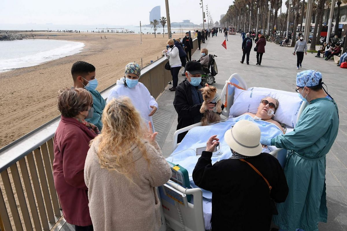 Friends, neighbours and medical personnel surround COVID-19 patient, Marta Pascual, 72, as she gets some fresh air at the Barceloneta beach esplanade outside Hospital del Mar in Barcelona on March 4, 2021.