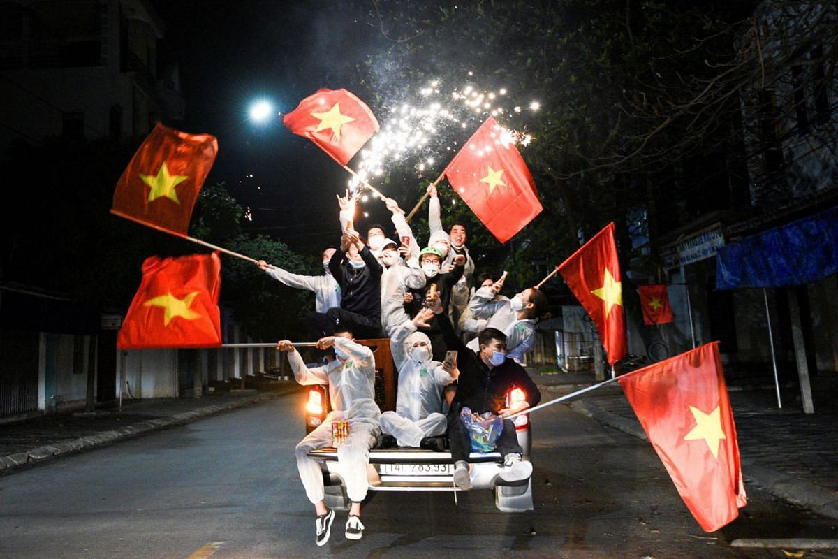 Residents come out to celebrate with national flags and fireworks after Hai Duong authorities end 34 days of social distancing amid the spread of the coronavirus disease in Chi Linh city, Hai Duong province, Vietnam, March 3, 2021.