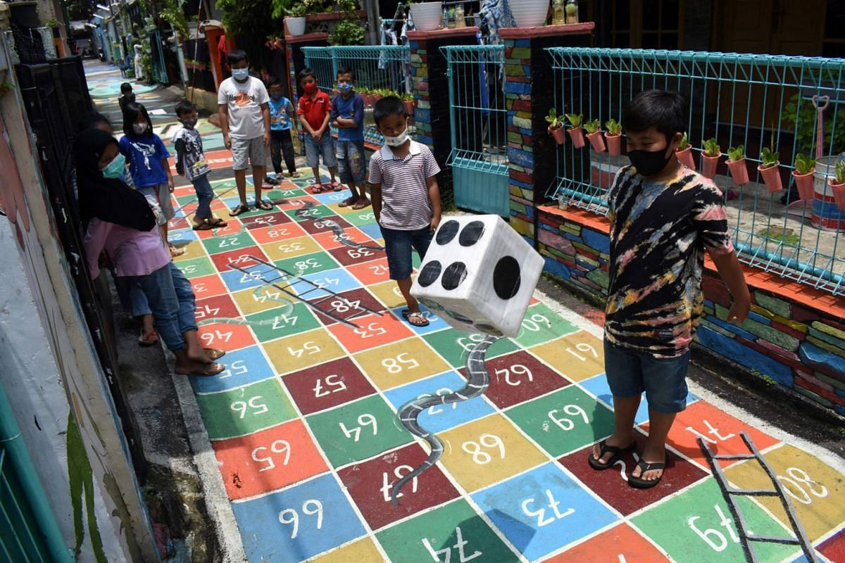 Children gather to play along a path painted with various children's games at a neighbourhood in Bandung on March 4, 2021.