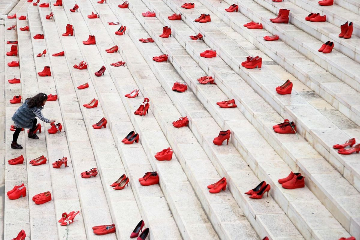 A girl puts flowers at an installation of women's red shoes displayed on staircase, as a symbol to denounce violence against women, at Durresi main square in Tirana, on International Women's Day, on March 8, 2021.