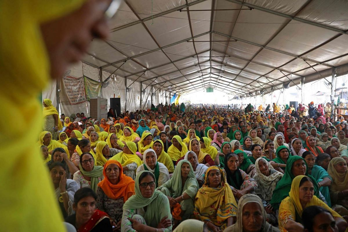 Women farmers listen to a speaker as they continue to demonstrate against the central government's recent agricultural reformation at the Delhi-Haryana state border, in Singhu on March 8, 2021.