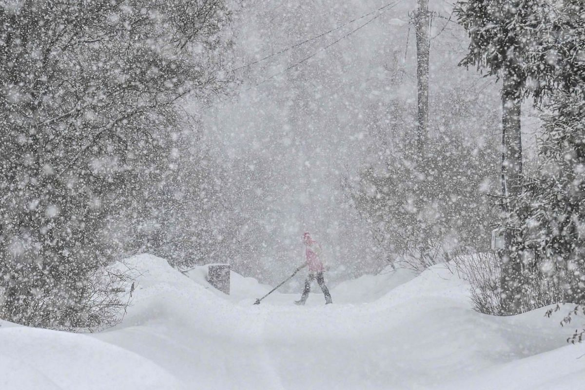 A man cleans a street during heavy snowfalls in the village of Zykeyevo some 45 km outside Moscow, on March 8, 2021.