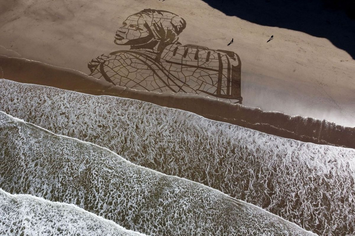 WaterAid and Sand In Your Eye giant sand portrait is seen on Whitby Beach, Britain, on March 15, 2021. The 60m wide drawing by artist Jamie Wardley shows a child carrying water on dry, cracked ground next to the rising tide, to highlight the impact c