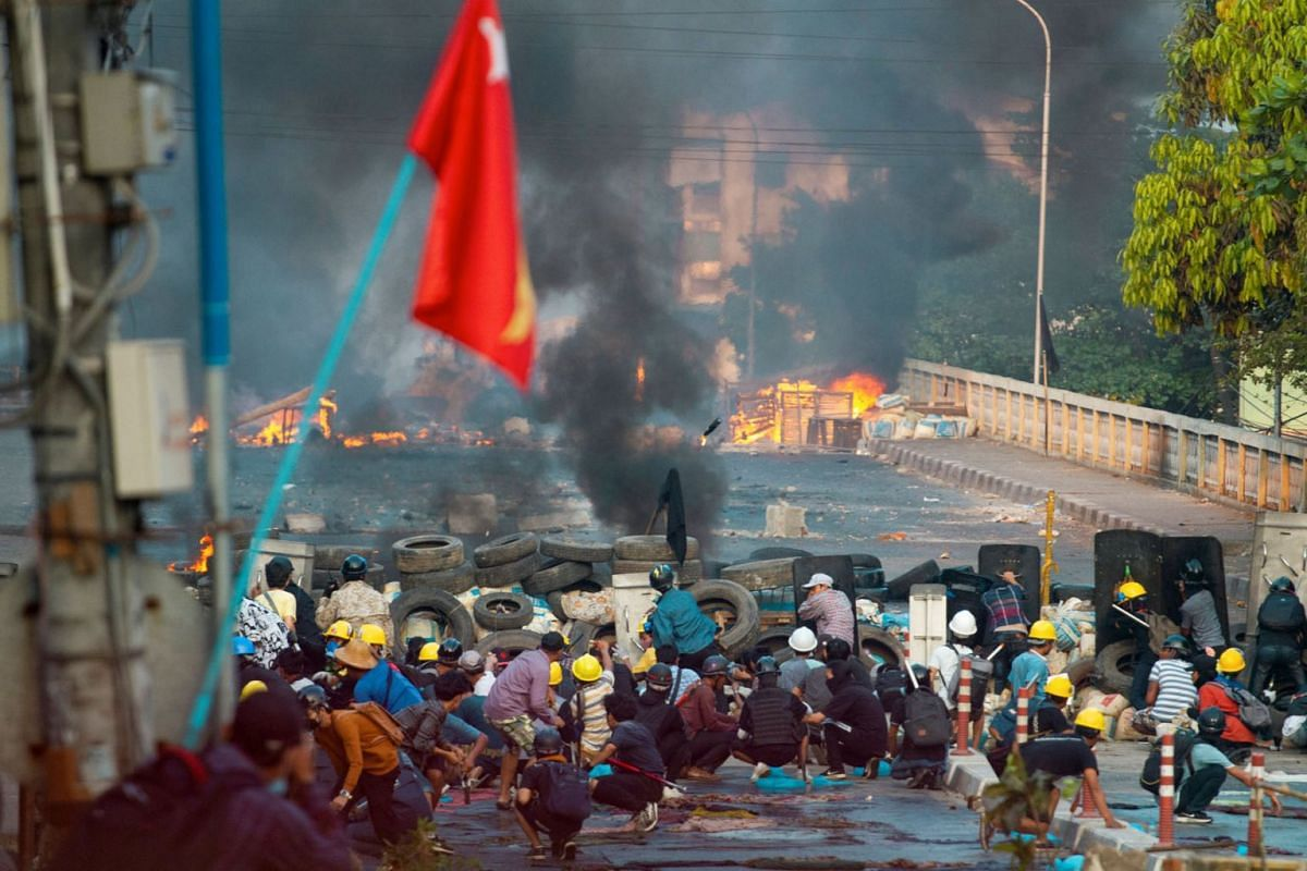Anti-coup protesters take cover at a barricade as they clash with security forces on Bayint Naung Bridge in Mayangone, Yangon, Myanmar, on March 16, 2021.