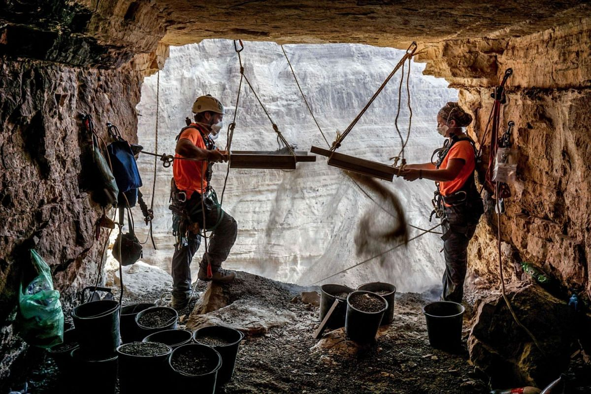 A handout picture made available through the Israeli Antiquities Authority (IAA) on March 16, 2021, shows a picture taken on October 28, 2019, of archaeologists Hagay Hamer (L) and Oriah Amichai sifting soil during excavations in the Cave of Horror i