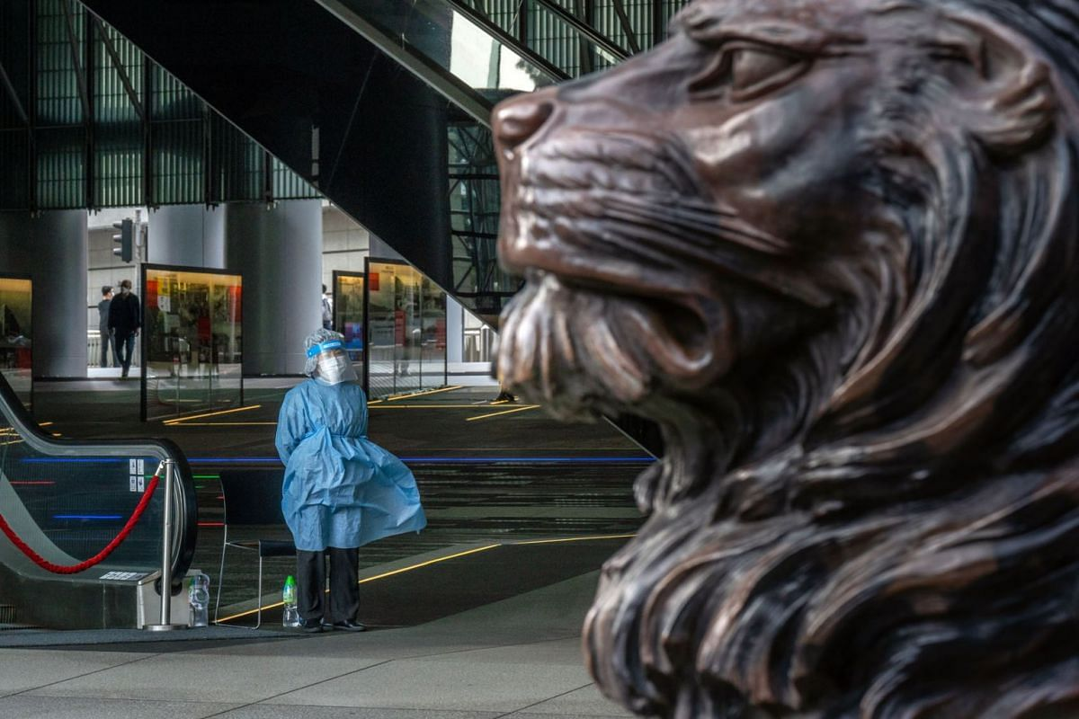 A security guard wearing personal protective equipment (PPE) stands guard next to an escalator at the HSBC Holdings Plc headquarters building, temporary closed due to multiple coronavirus cases, in Hong Kong, China, on March 17, 2021.