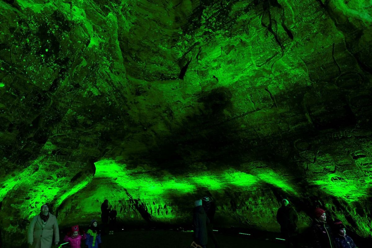 People visit the Gutman's cave, the largest in the Baltic countries, which is illuminated in green during Ireland's annual Global Greening initiative to mark St. Patrick's Day in Sigulda, Latvia, on March 16, 2021.