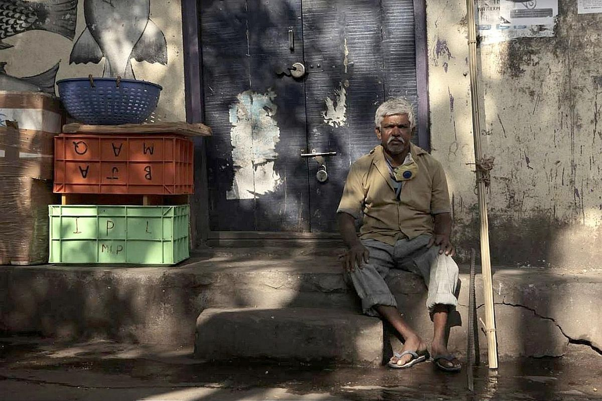 ABOVE: Mr Pedanna G, 55, waiting for work at his usual place near the fish market of a middle-class neighbourhood in south Bangalore. He is what is known in India as a manual scavenger, someone who cleans toilets, drains and manholes by hand. RIGHT: