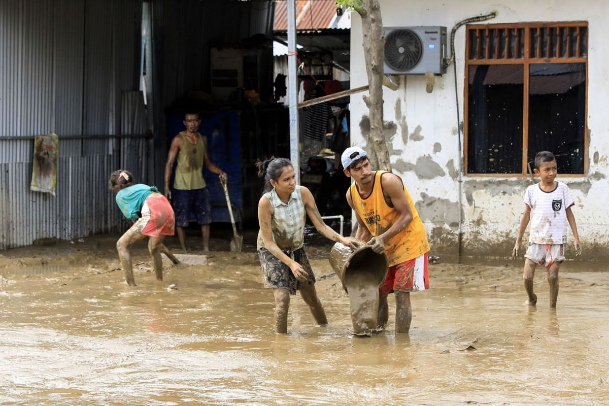 People clear mud off their house in the aftermath of floods in Dili, East Timor, also known as Timor Leste, on April 5, 2021.