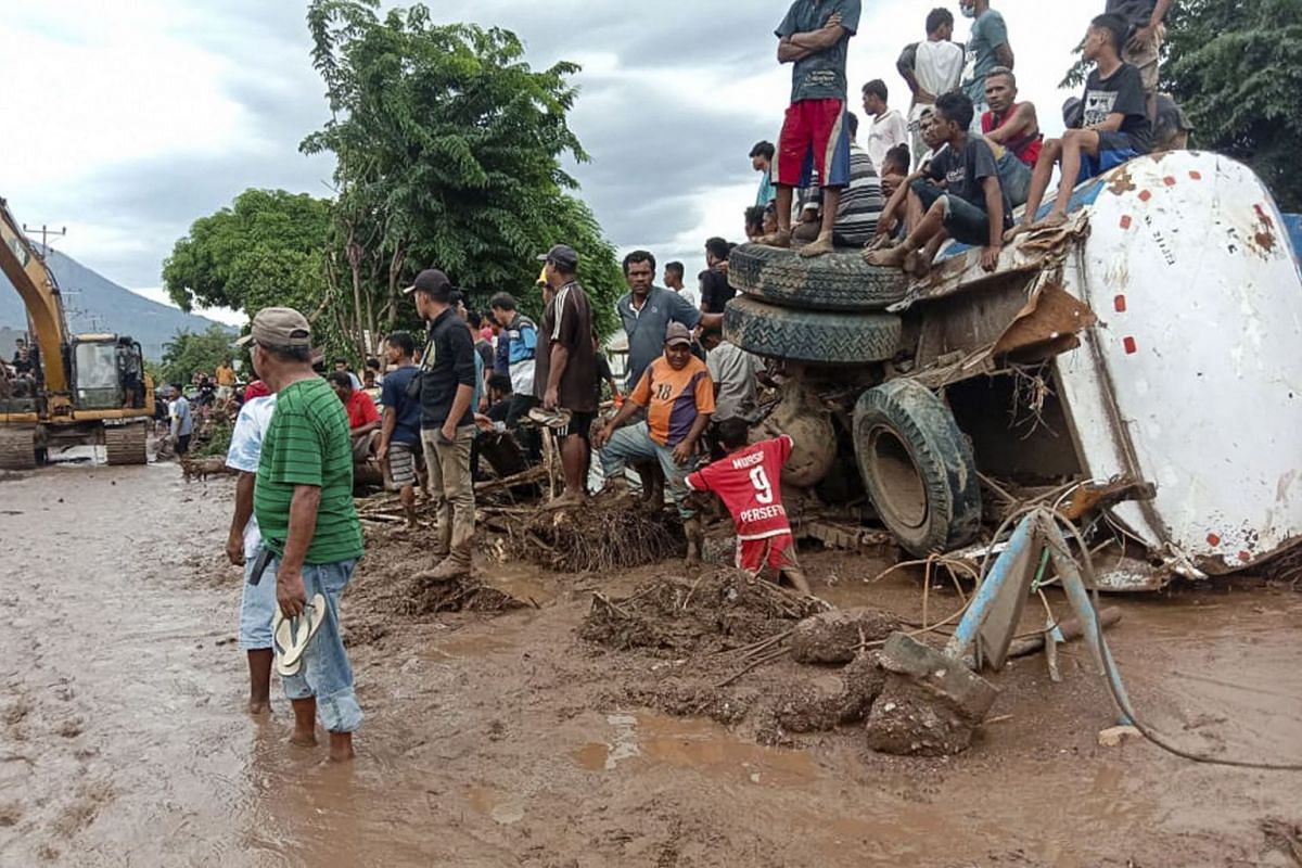 People gather near an overturned tanker truck after a flash flood hit their village in Adonara, East Flores, Indonesia, on April 6,  2021.