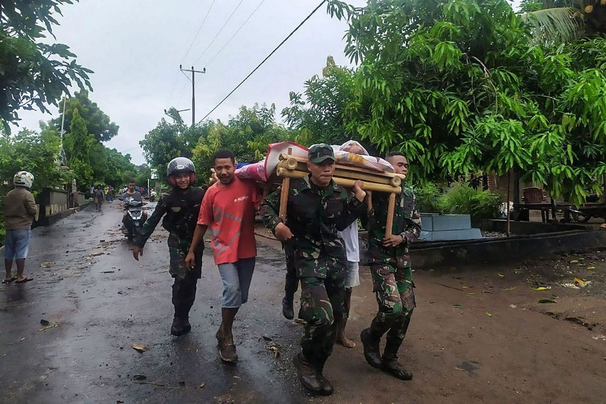 Villagers carry the body of a victim after flash floods in Lembata, East Flores, on April 5, 2021, as torrential rains triggered floods and landslides.