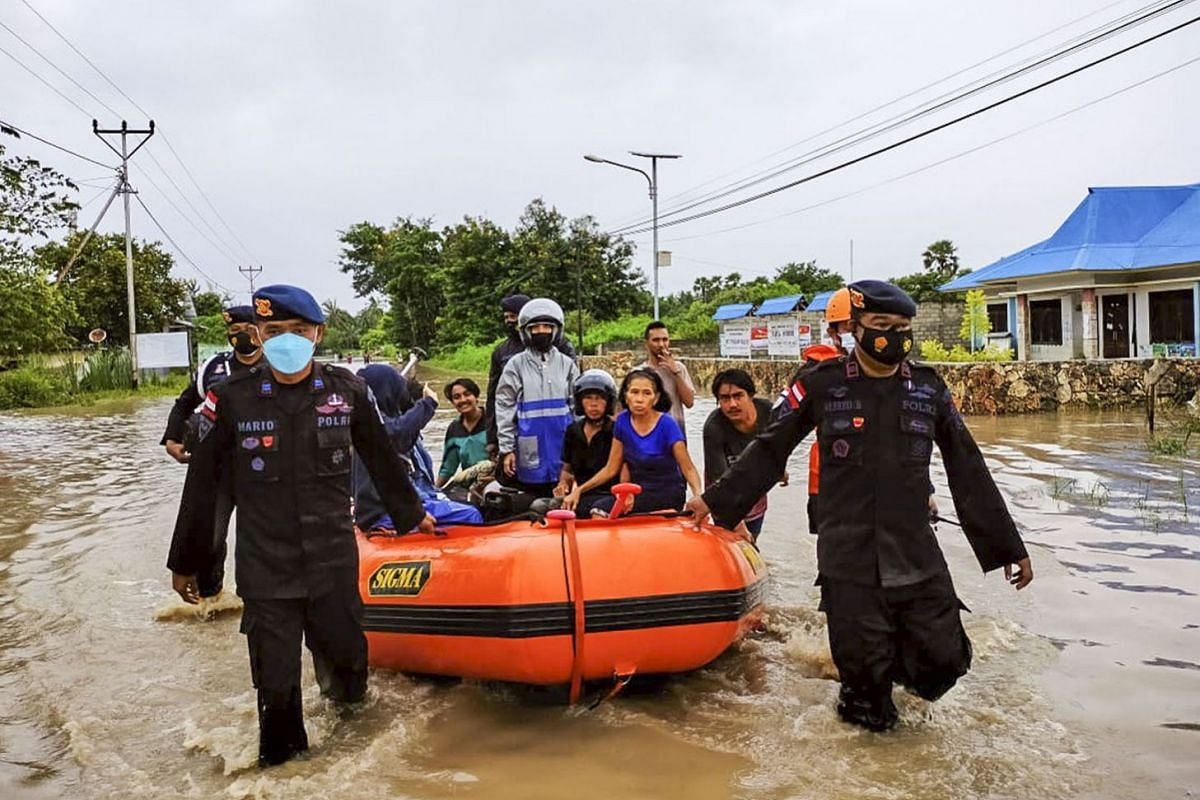 A handout photo made available by the Indonesian National Search and Rescue Agency (BASARNAS) shows rescuers evacuating people on a rubber boat during a flood in Waingapu, East Nusa Tenggara, Indonesia, on April 5, 2021.