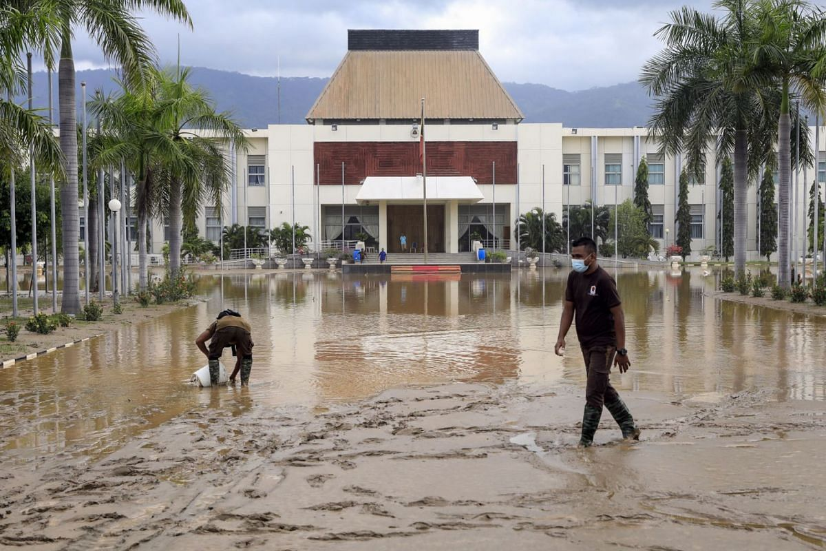 Workers clear mud off a road outside the Nicolau Lobato Presidential Palace in the aftermath of floods in Dili, East Timor, also known as Timor Leste, on April 5, 2021.