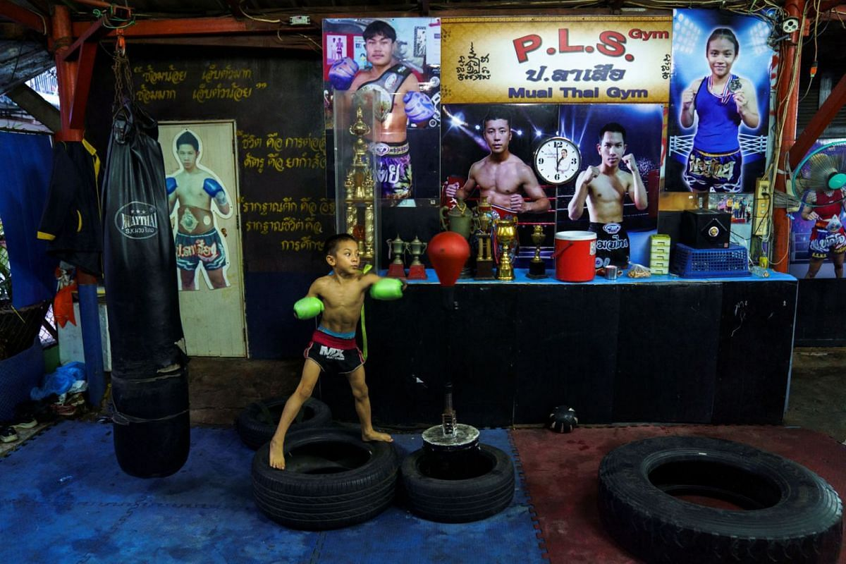 "Child Muay Thai boxer Pornpattara Peachurai, known as Tata Por Lasua, his fighter name, 9, trains at a gym in Bangkok, Thailand, October 3, 2020. ""All the money from boxing, the regular payment and the tips, it all goes to mum,"" said Peachurai. ""I'm"