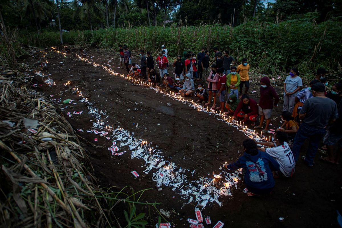 People light candles at a mass-burial ground for landslide victims triggered by tropical cyclone Seroja in East Flores, East Nusa Tenggara province, Indonesia April 7, 2021, in this photo taken by Antara Foto.