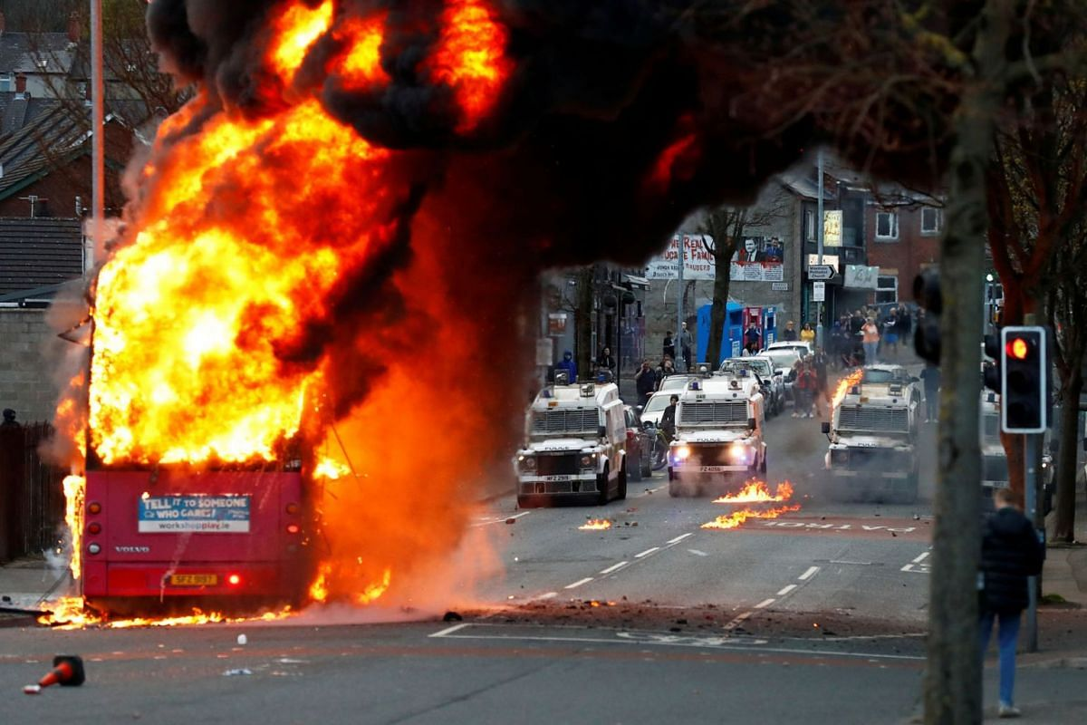 Police vehicles are seen behind a hijacked bus burns on the Shankill Road as protests continue in Belfast, Northern Ireland, April 7, 2021.