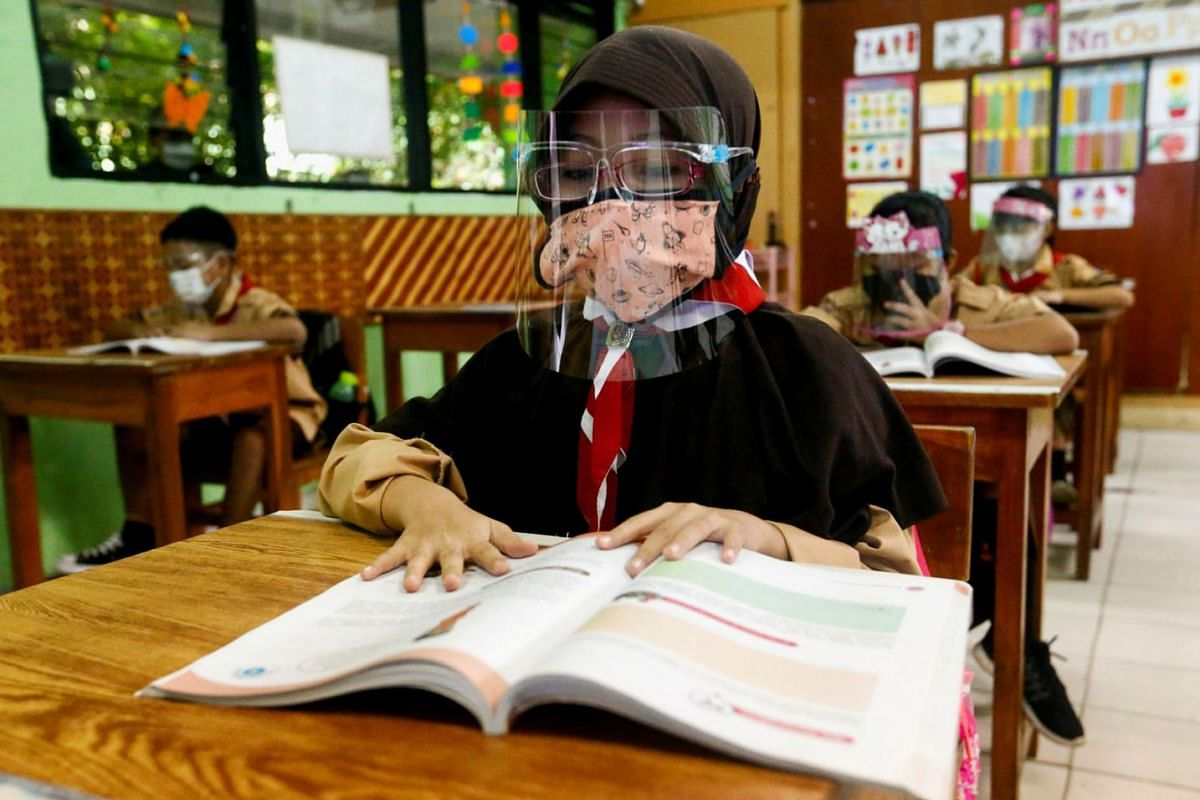 Elementary school students wearing face masks and face shields attend class as schools reopen amid the Covid-19 pandemic, in Jakarta, Indonesia, on April 7, 2021.