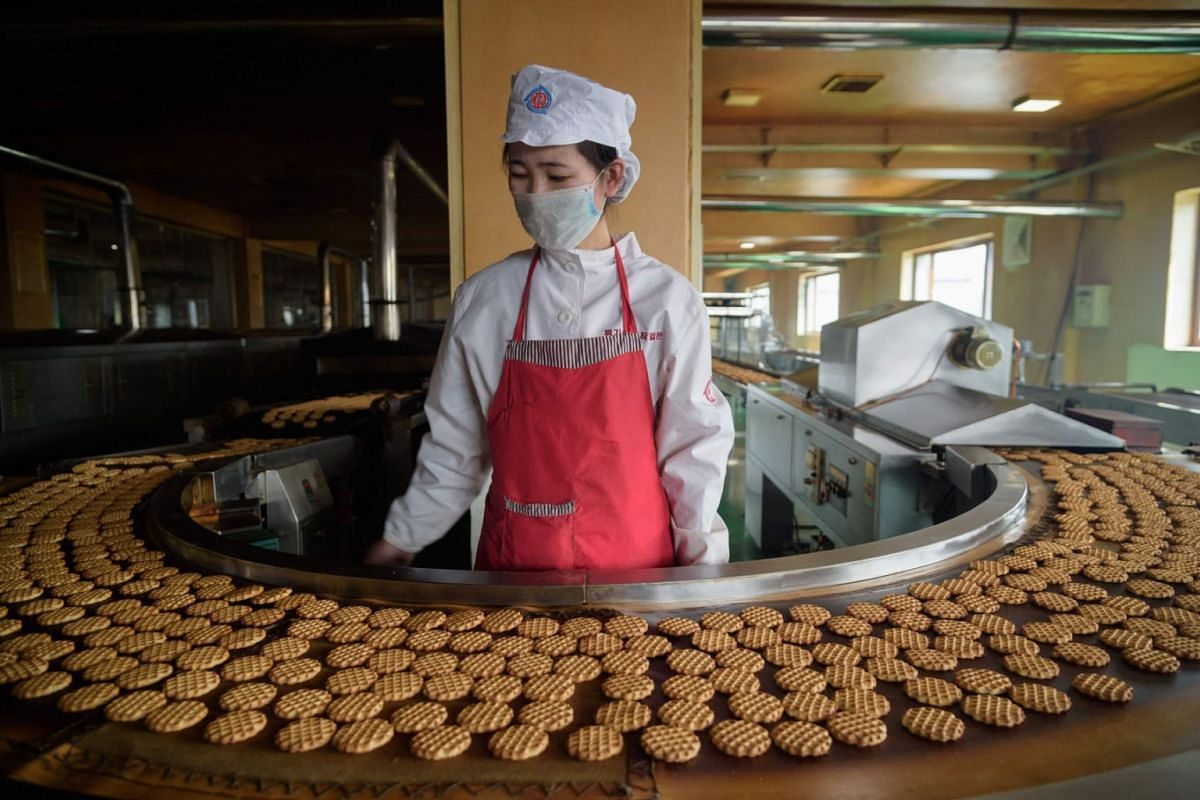 """A worker stands before a machine on a production line for """"Taeha"""" brand cakes at the Unha Taesong Foodstuff Factory in Pyongyang on April 6, 2021."""
