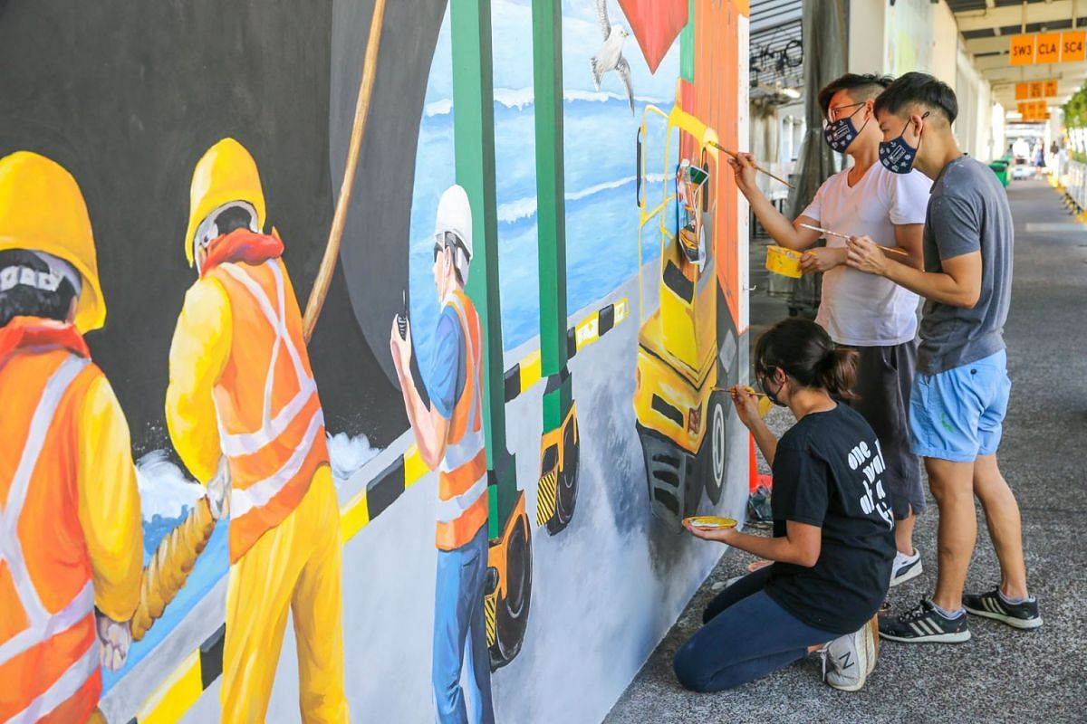 Mr Jaxton Su, 33, Mr Klein Aw, 21, and Ms Elizabeth Goh, 26, touching up the mural at PSA's Pasir Panjang Terminal on April 7, 2021. The Jurong Port mural highlights the vital role of maritime personnel in maintaining international trade and supply