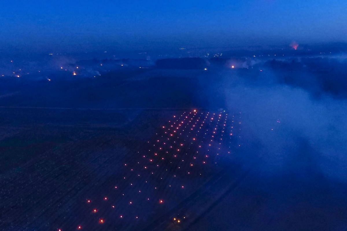 This photograph taken at dawn on April 7, 2021 shows an aerial view of smoke rising from fires lit in the vineyards to protect them from frost at the heart of the Vouvray vineyard in Touraine.