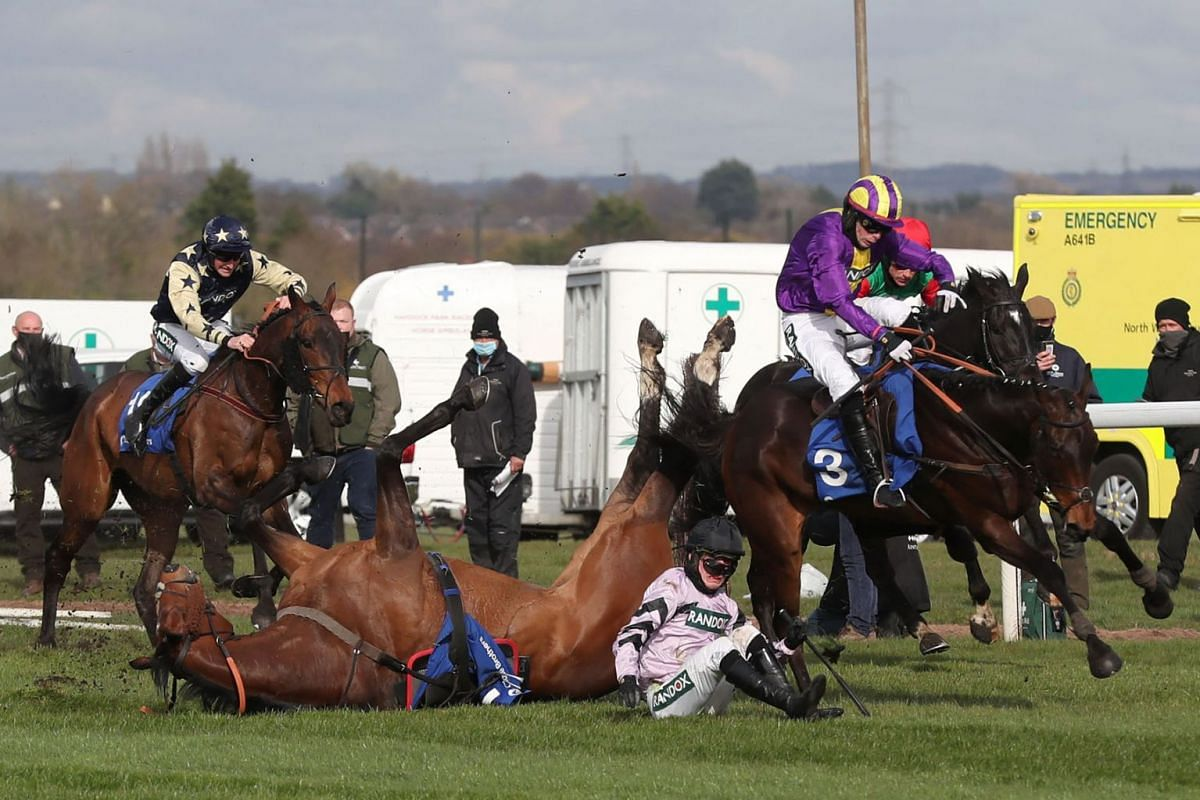 Editeur Du Gite ridden by Joshua Moore (C) falls during the Close Brothers Red Rum Handicap Chase on the first day of the Grand National Festival at Aintree Racecourse in Liverpool, north west England on April 8, 2021.