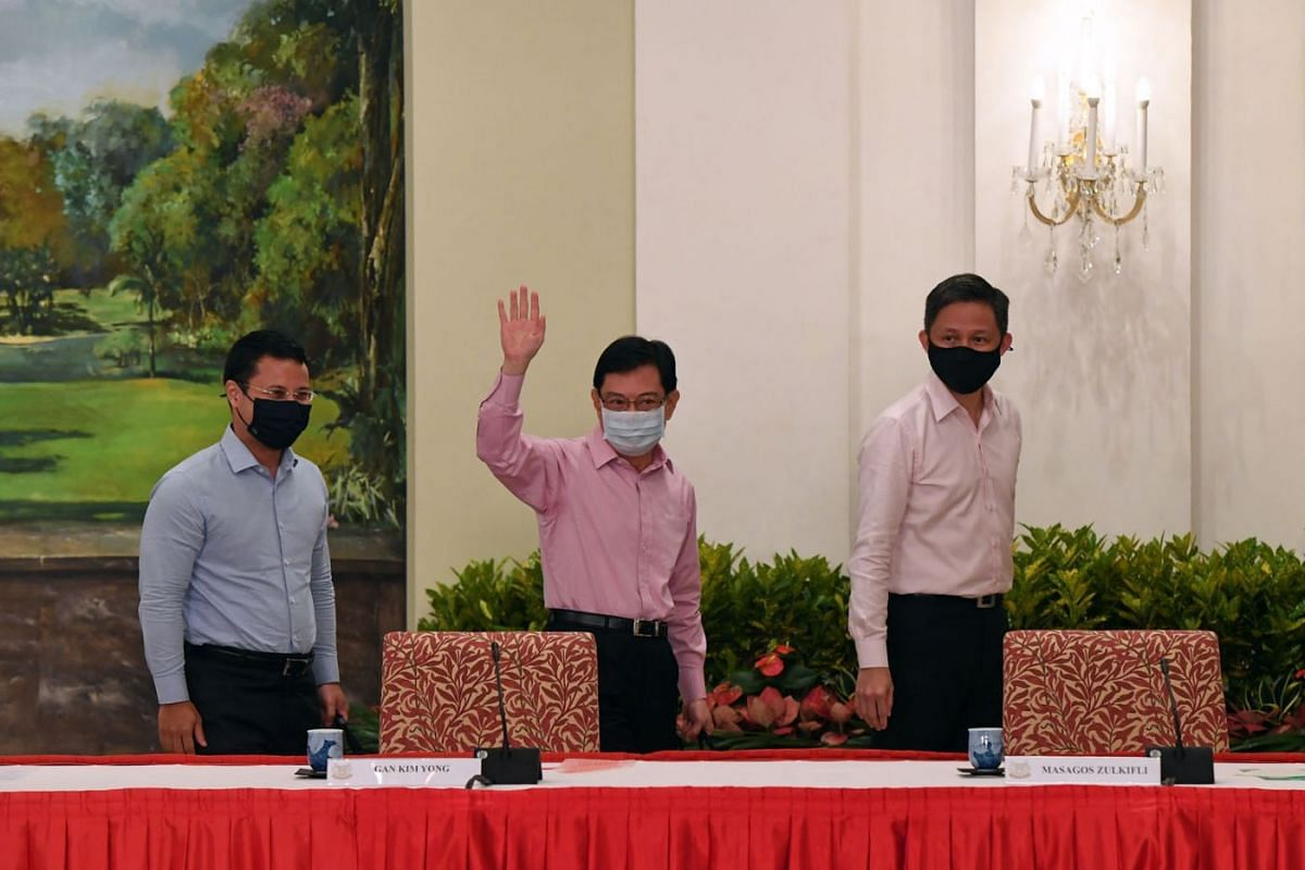 Deputy Prime Minister Heng Swee Keat waves as he leaves a press conference, flanked by Ministers Desmond Lee (left) and Chan Chun Sing (right), held at the Istana on April 8, 2021. DPM Heng has decided to step aside as leader of the People's Action P
