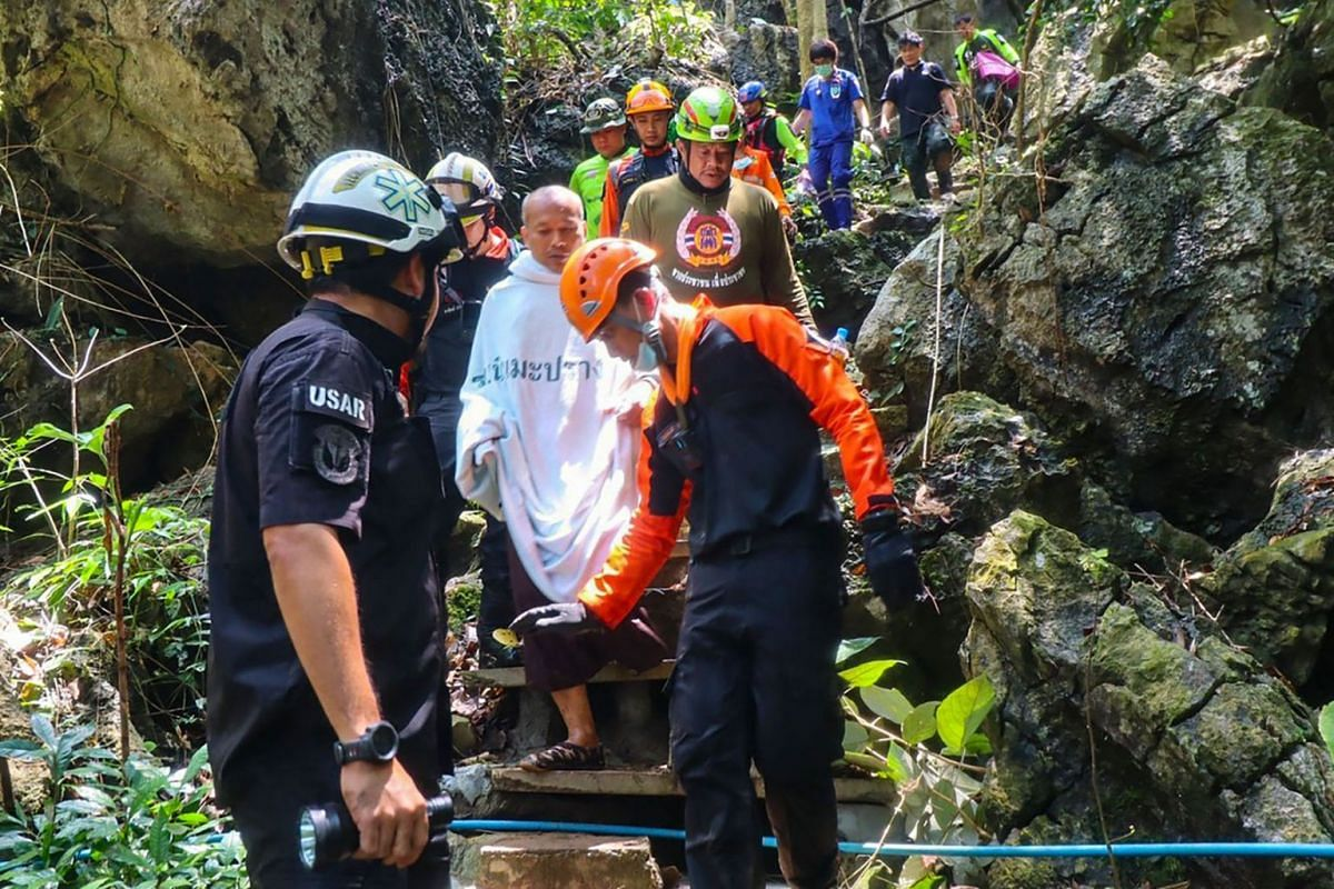 This handout from the Prasatbunyasathan Foundation taken on April 7, 2021 ,shows Buddhist monk Manas Kemgoh (C in white), who had been trapped in the flooded Phra Sai Ngam cave while meditating, walking after he was freed by rescue workers in Thailan