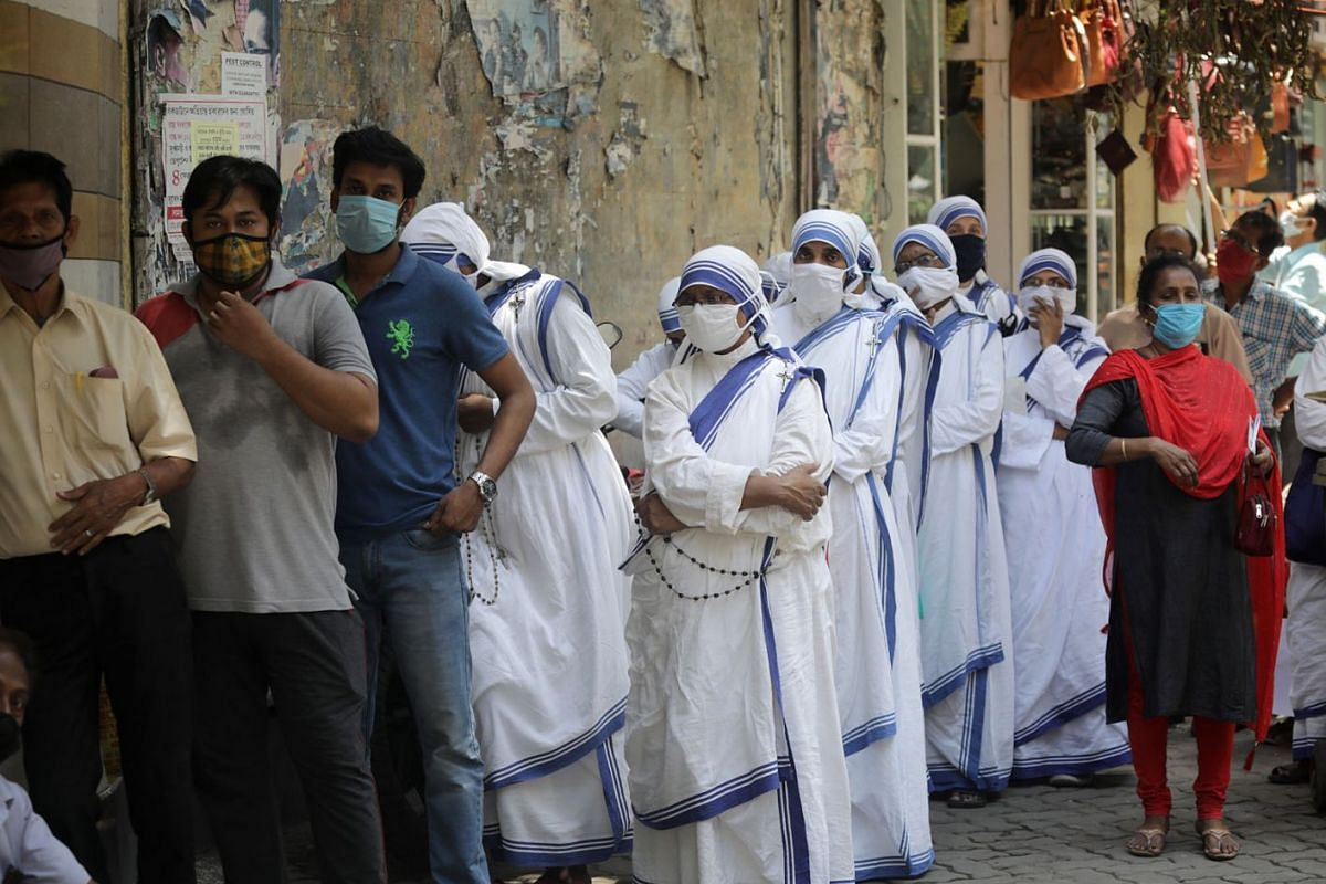 Missionaries of Charity nuns and locals wait for a Covid-19 test at a centre in Kolkata on April 19, 2021.