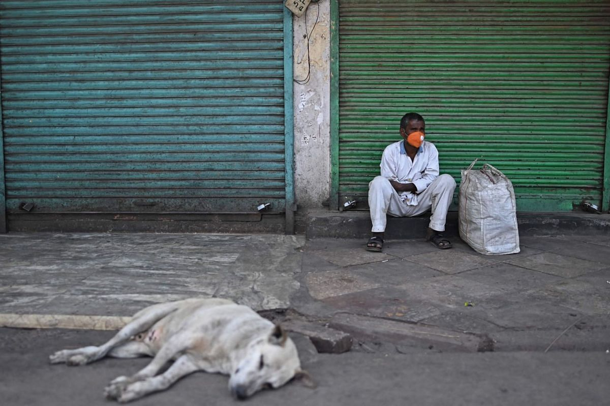 A man sits besides shops with the shutters closed amid a lockdown in New Delhi on April 17, 2021.