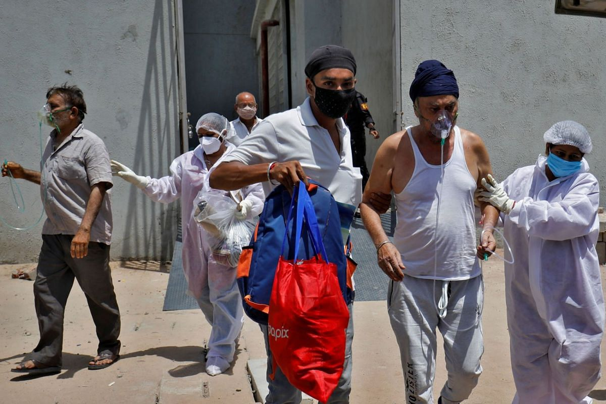 Patients wearing oxygen masks are moved to a hospital amid the spread of Covid-19 in Ahmedabad on April 21, 2021.