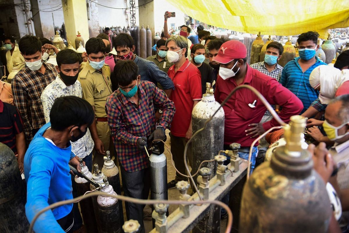People refill medical oxygen cylinders for Covid-19 patients at an oxygen refilling station in Allahabad on April 20, 2021.