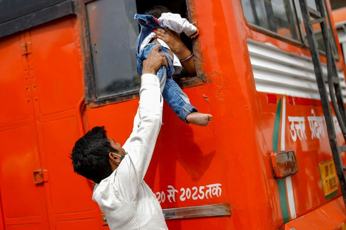 A migrant worker lets his son climb through a bus window as they try to make their way home to their village on April 20, 2021.